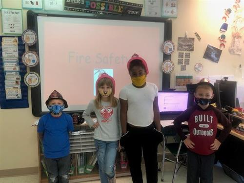 Four students posing in fire hats